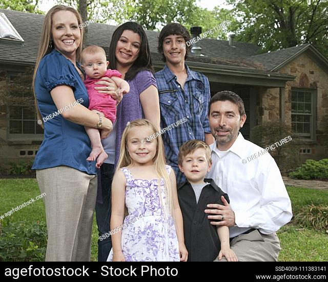 Family standing in front yard together