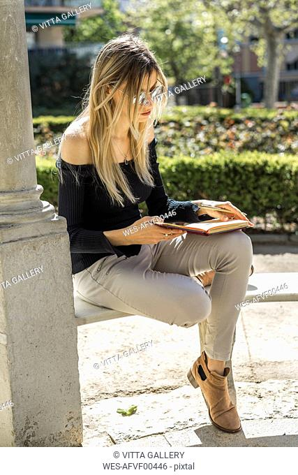 Young woman with notebook sitting on bench