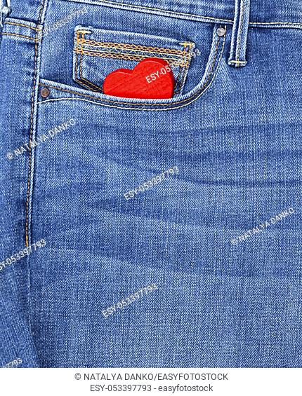 red heart lies in the front pocket of blue jeans, full frame, close up