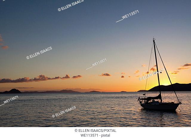 Silhouette of sailboat moored in water with orange glow of sunset lighting up the clouds and sky in Caribbean