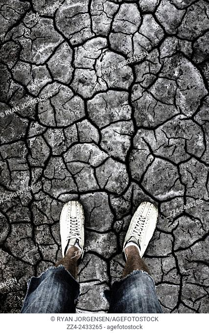 Feet of an Australian man standing in an arid dry lake bed in a footnote of rising humidity from climate change. Taken Queensland, Australia