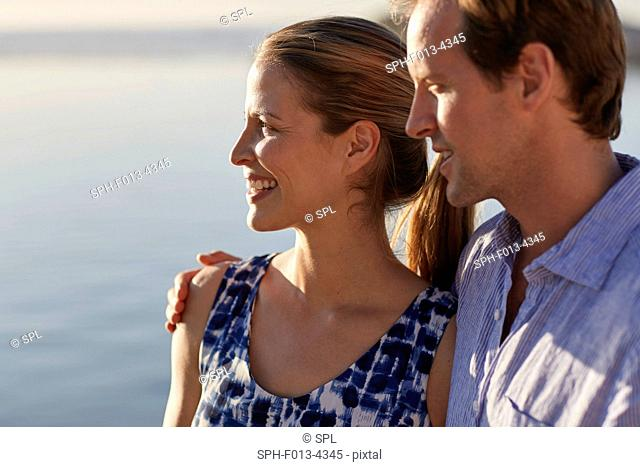 MODEL RELEASED. Couple looking at view, man with arm around woman