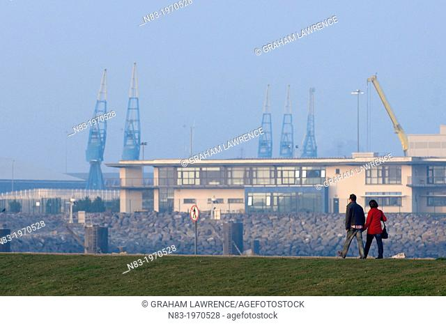 A couple walk along Locks Road, Cardiff Bay, Glamorgan, Wales, UK