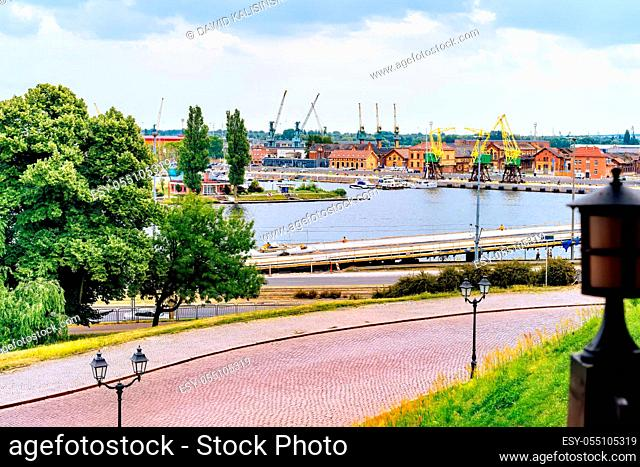 View from Rampart of Brave on Old Town quay in Szczecin docklands with Odra River, rustic dock cranes called Dzwigozaury and harbour in background