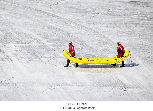 Search and rescue workers, wearing cold water survival gear on the frozen Assiniboine River. Winnipeg, Manitoba, Canada
