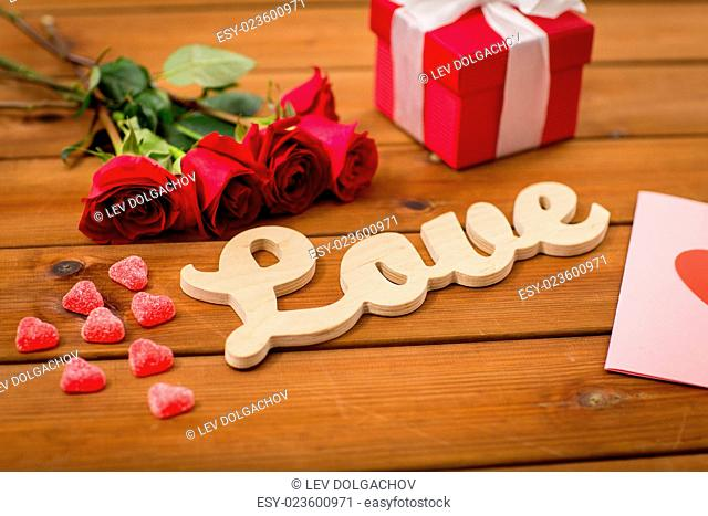 romance, valentines day and holidays concept - close up of word love, gift box, red roses and greeting card with heart-shaped candies on wood