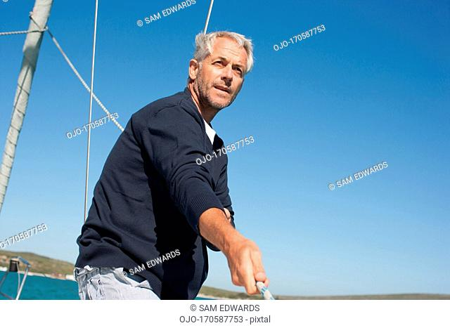 Man pulling rope on deck of boat