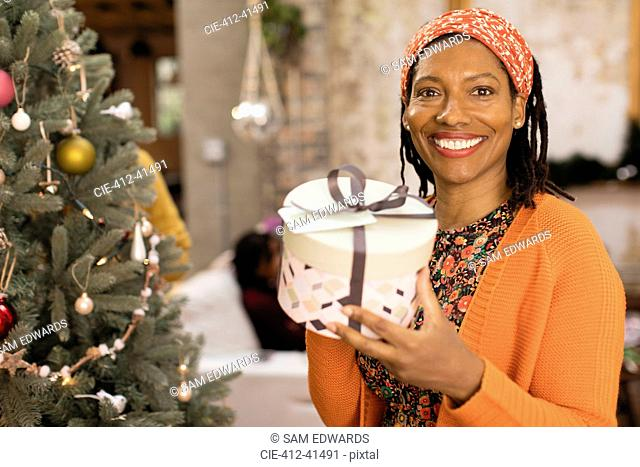 Portrait smiling, confident woman holding gift next to Christmas tree