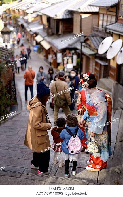 Two Maiko, Geisha apprentices, in colorful kimono on an old street in Higashiyama, Kyoto, Japan 2017