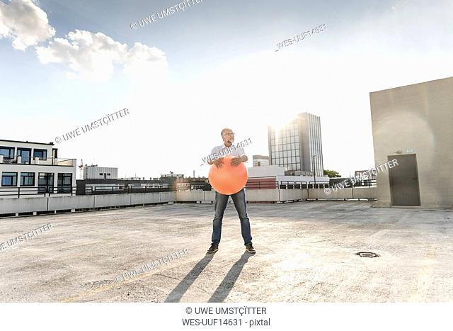 Mature man playing with orange fitness ball on rooftop of a high-rise building