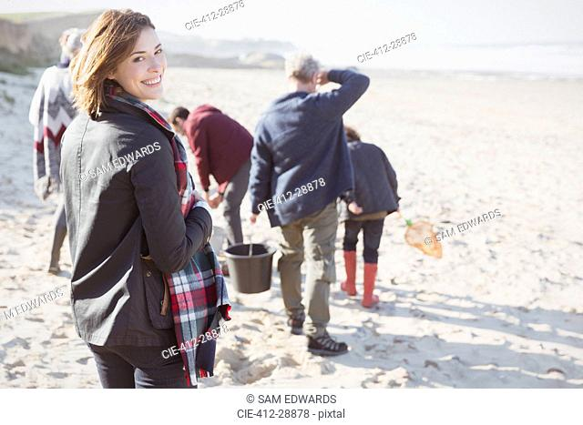 Portrait smiling woman walking on sunny beach with family