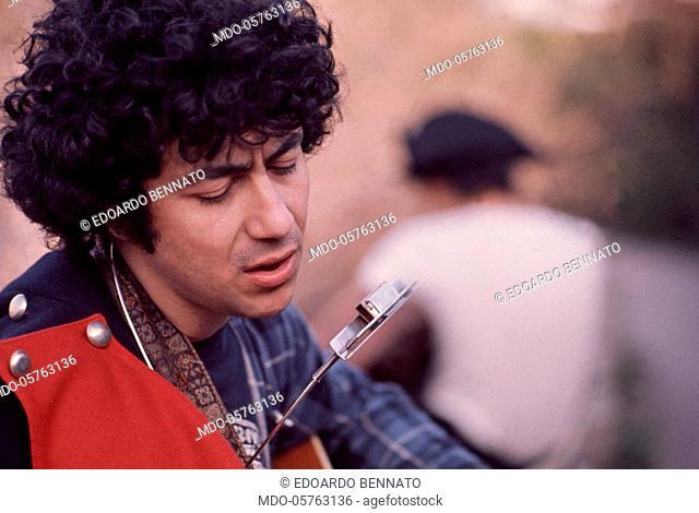Italian singer-songwriter Edoardo Bennato singing and playing the guitar. Italy, 1970s