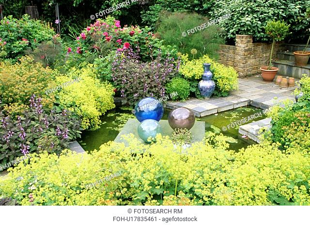 Glass globes and small pond surrounded by Alchemilla Mollis
