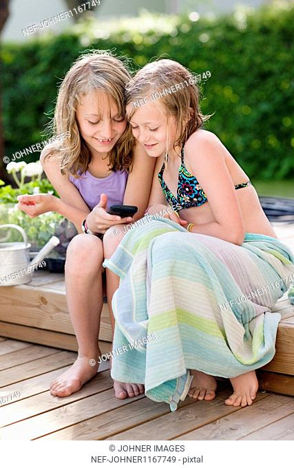 Two girls sitting in garden and texting on mobile phone