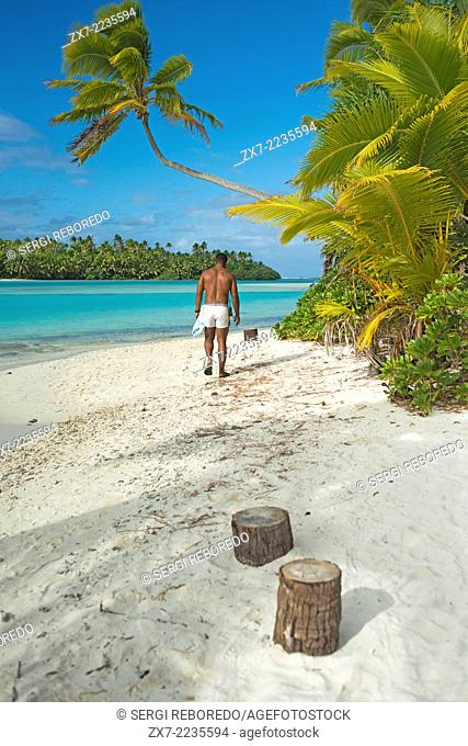 Aitutaki. Cook Island. Polynesia. South Pacific Ocean. An inhabitant of the island takes up a coconut palm tree on the beach in One Foot Island