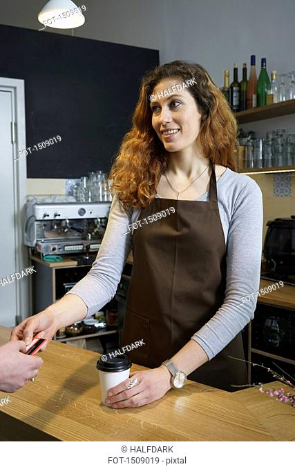 Owner accepting credit card from customer at cafe