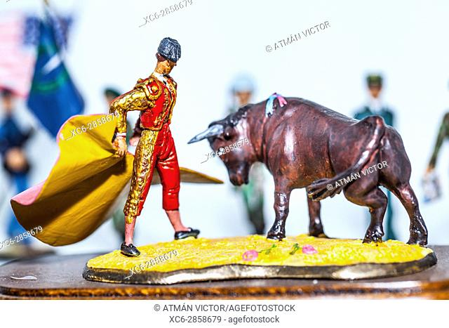 Tiny miniature vintage spanish bullfighter with bull figurine standing