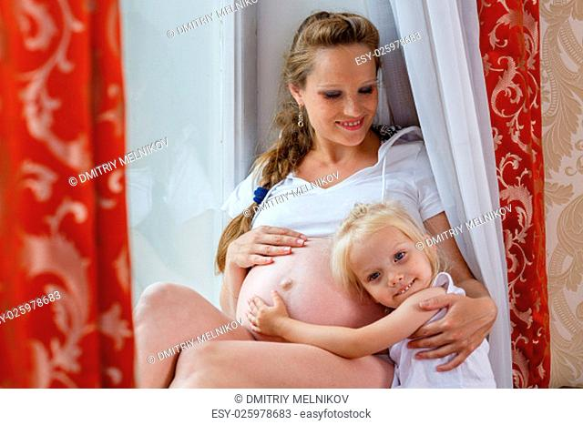Pregnant woman with her little daughter sit near window in the room. Happy family