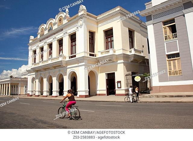 Cyclists in front of the Tomas Terry Theatre at Jose Marti Park, Plaza De Armas, Cienfuegos, Cuba, West Indies, Central America