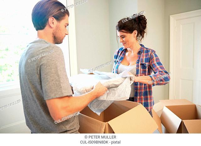 Couple packing belongings into cardboard box