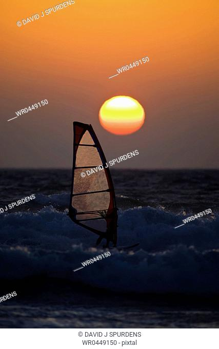 A windsurfer rides the ocean waves at sunset