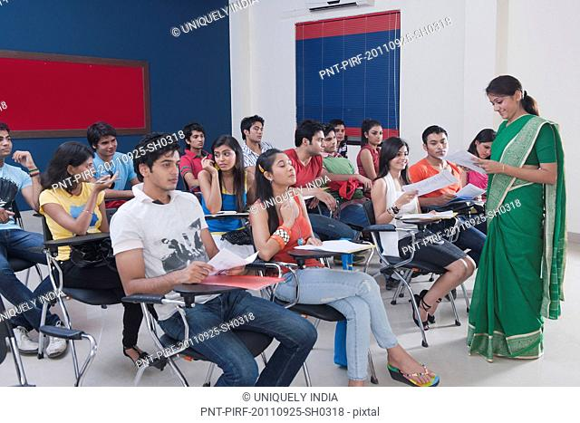 Female lecturer and students in a examination hall