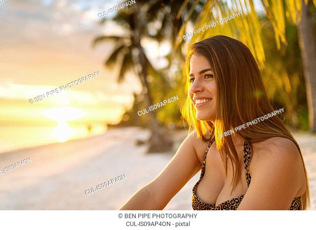 Young woman on Anda beach at sunset, Bohol Province, Philippines