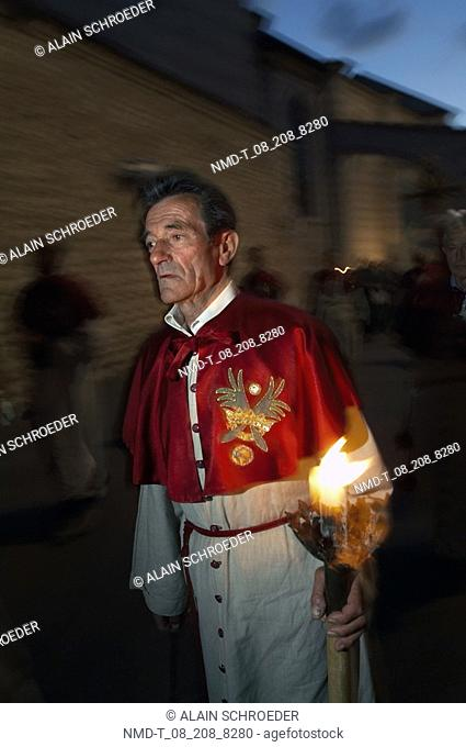 Priest carrying a lit up candle at a procession, Assisi, Umbria, Italy