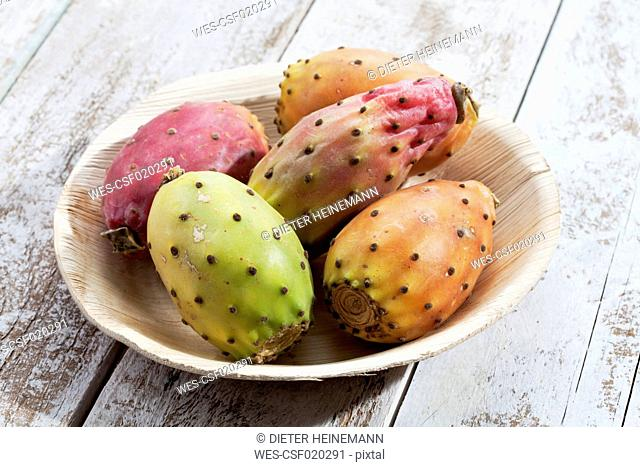Prickly pears (Opuntia ficus-indica) on plate made from palm leaves on white wooden table, studio shot