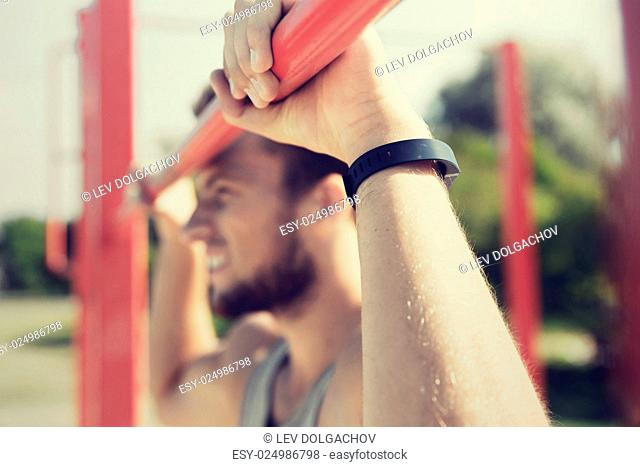fitness, sport, training and lifestyle concept - close up of young man with heart-rate watch bracelet exercising on horizontal bar in summer park