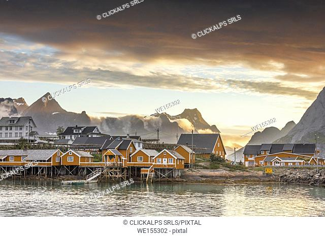 Sunset on the fishing village frames by rocky peaks and sea Sakrisoya Nordland county Lofoten Islands Northern Norway Europe