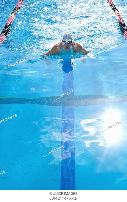 Male swimmer training in swimming pool, elevated view lens flare