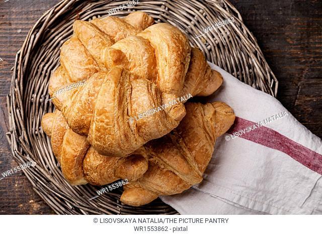Croissants in wicker tray on dark wooden background