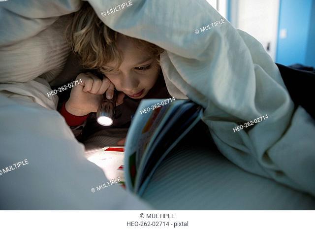 Boy reading book with flashlight under comforter
