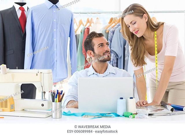 Fashion designers using laptop in studio