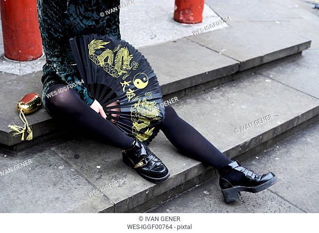 London, young woman with chinese fan in Chinatown, sitting on steps