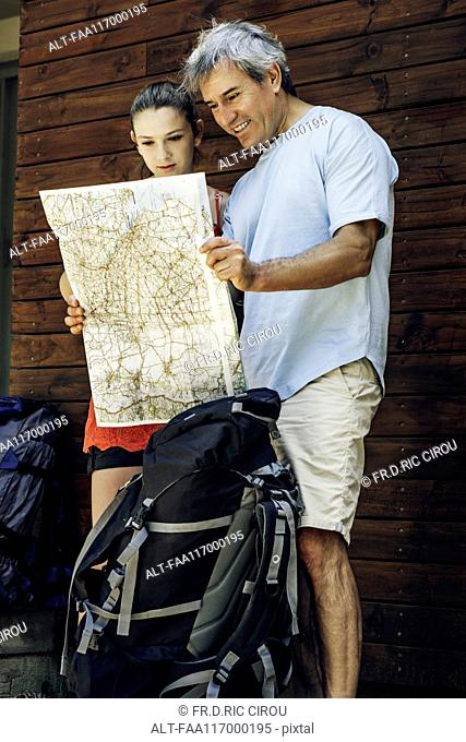 Father and daughter standing with map