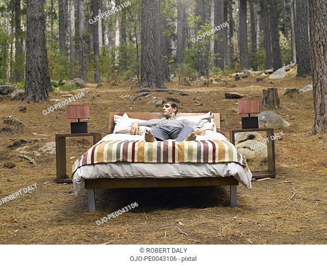 A man lying in a bed outdoors in the woods
