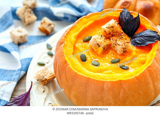 Pumpkin cream soup in a pumpkin on a white plate, selective focus