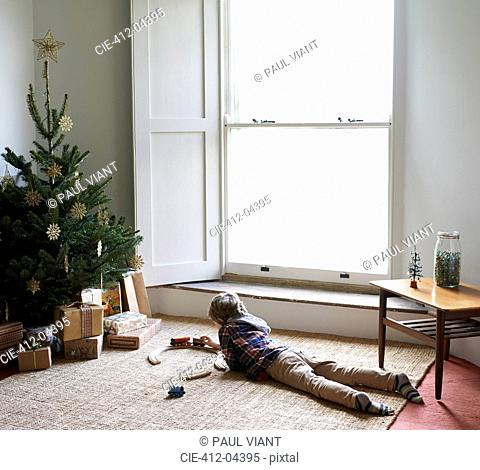 Boy playing with train by Christmas tree