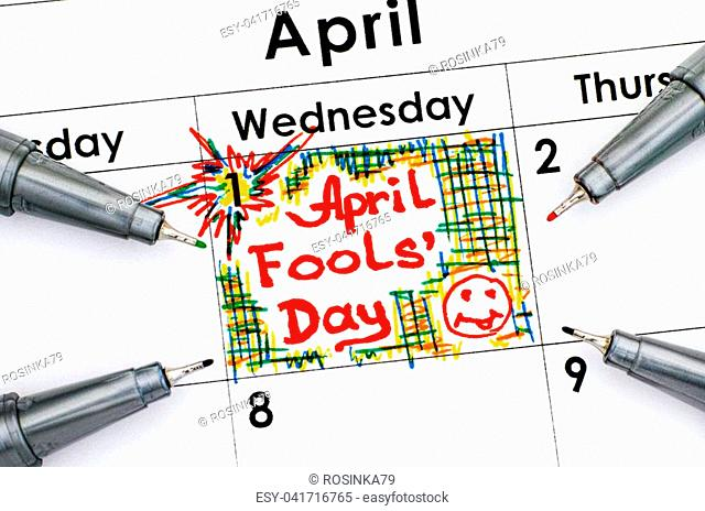 Reminder April Fools Day in calendar with four pens. Close-up