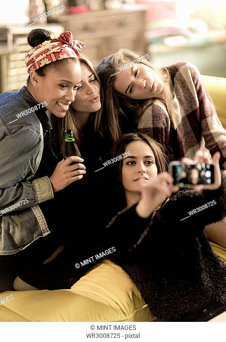 Four young women sitting on a sofa, smiling, taking a selfie, holding beer bottles