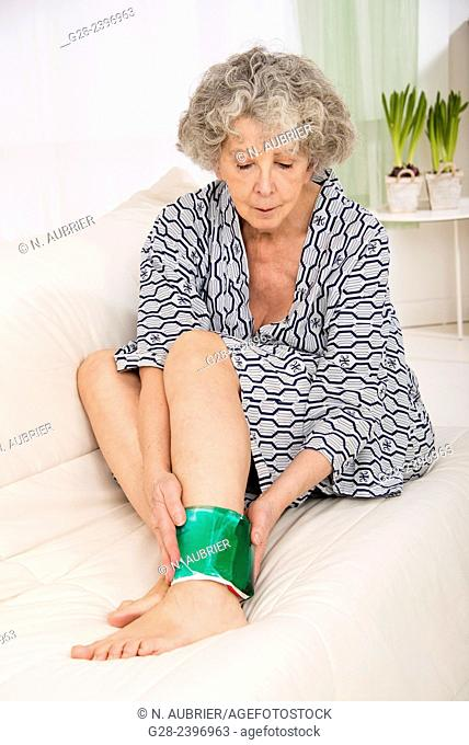 Beautiful senior woman holding a hot and cold gel compress around her ankle, sitting on a sofa, with plants in the background