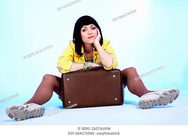 brunette with suitcase sitting