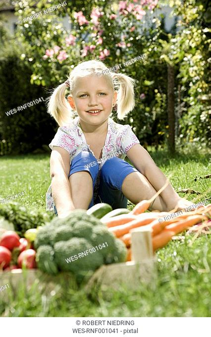 Germany, Bavaria, Girl sitting in vegetable gaeden, smiling, portrait