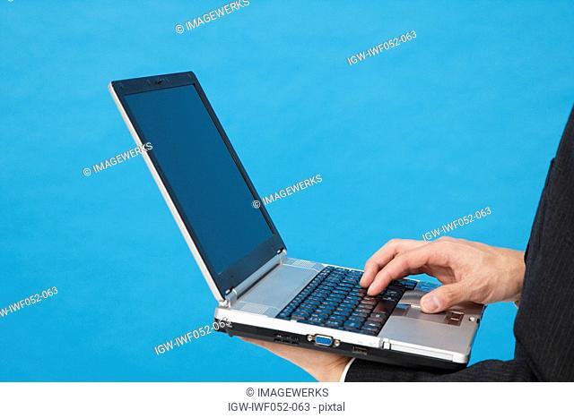 Young man using laptop, close-up