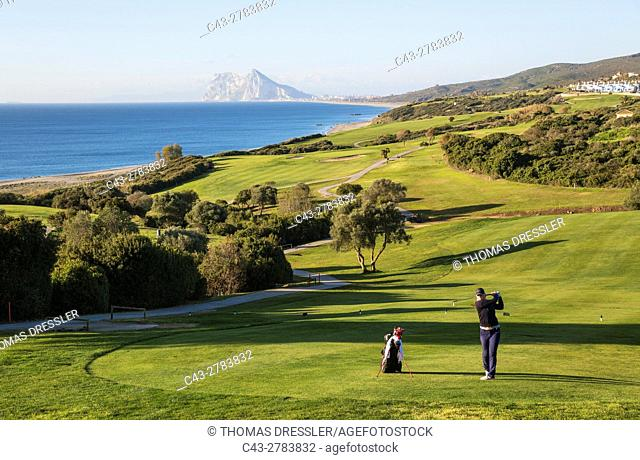 Golfer at the La Alcaidesa Golf Resort at the Mediterranean Sea with the Rock of Gibraltar (British) in the background. Cadiz province, Andalusia, Spain