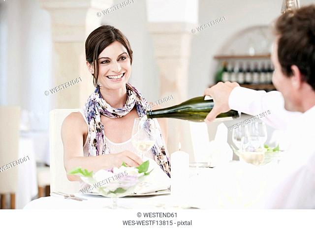 Couple in restaurant, man pouring wine into glass