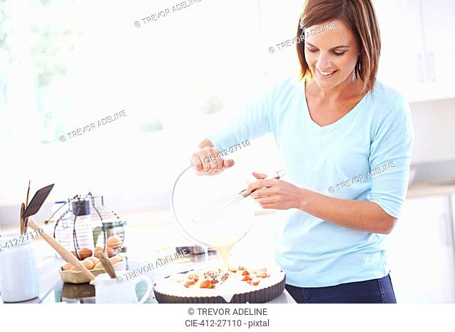 Woman cooking tomato quiche in kitchen