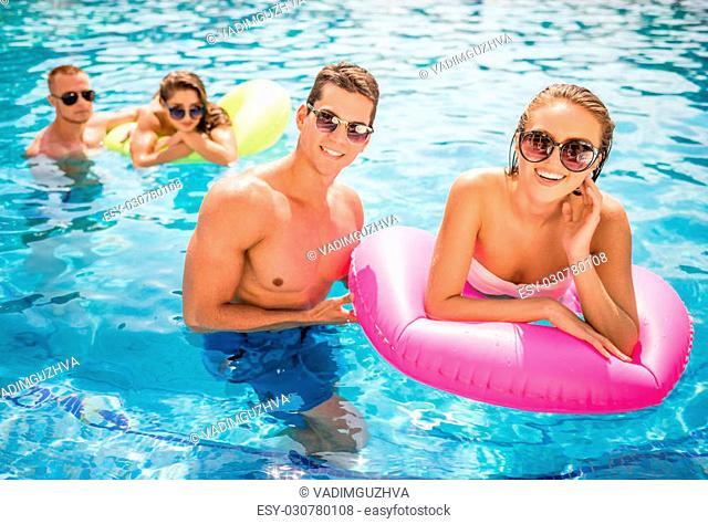 Beautiful young people having fun in swimming pool, smiling